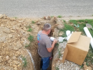 Randy connecting a new sewer drain to the city sewer under the street.